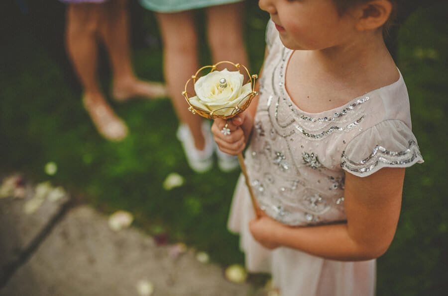 A flowergirl holds a flower outside the church