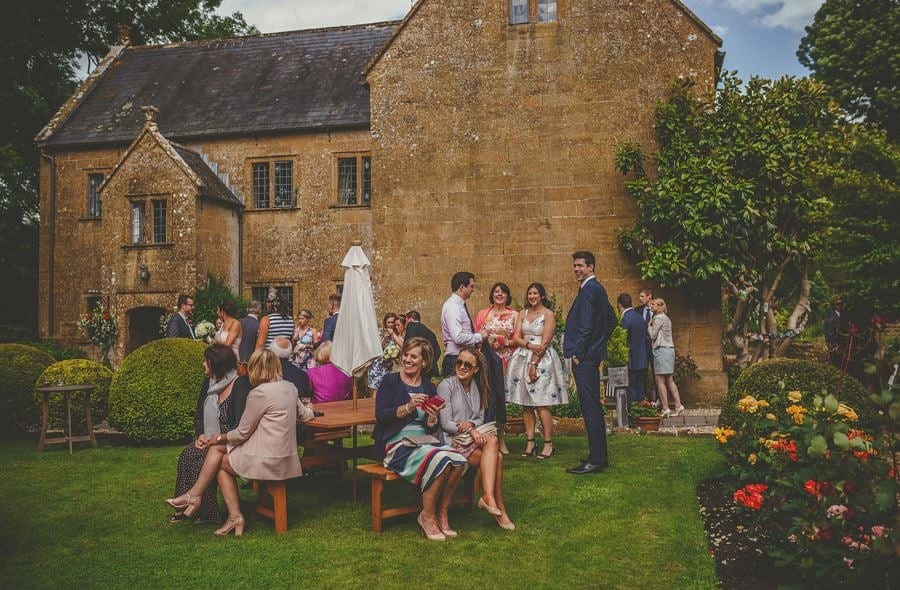 Wedding guests sit in the garden at the old bridge in petherton