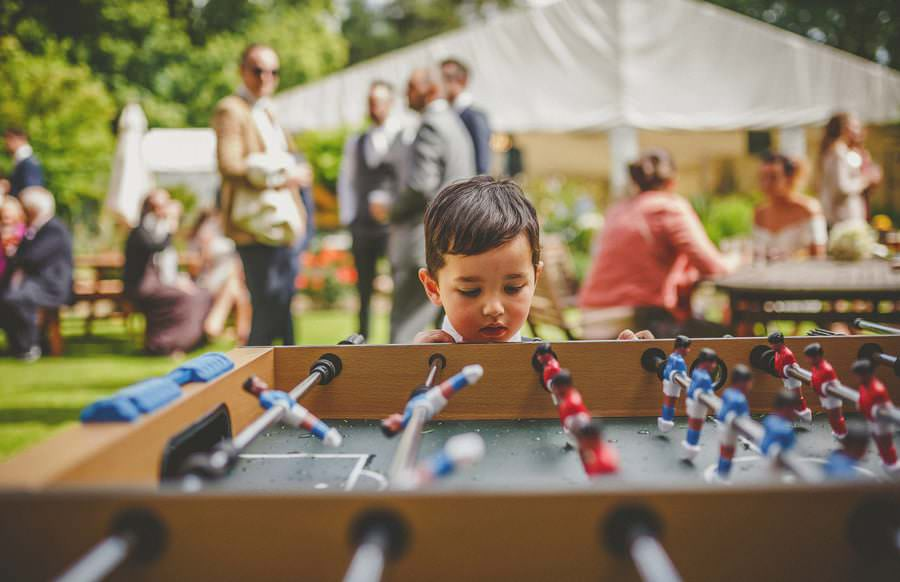 The grooms son looks at the table football in the garden