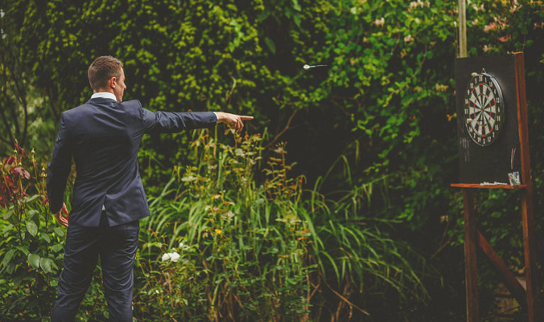 A man throws a dart at a board in the garden