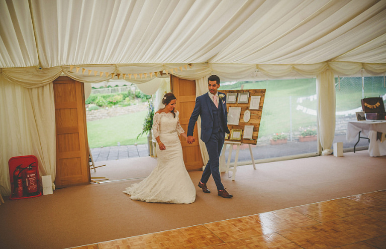 The bride and groom enter the marquee in the old bridge garden