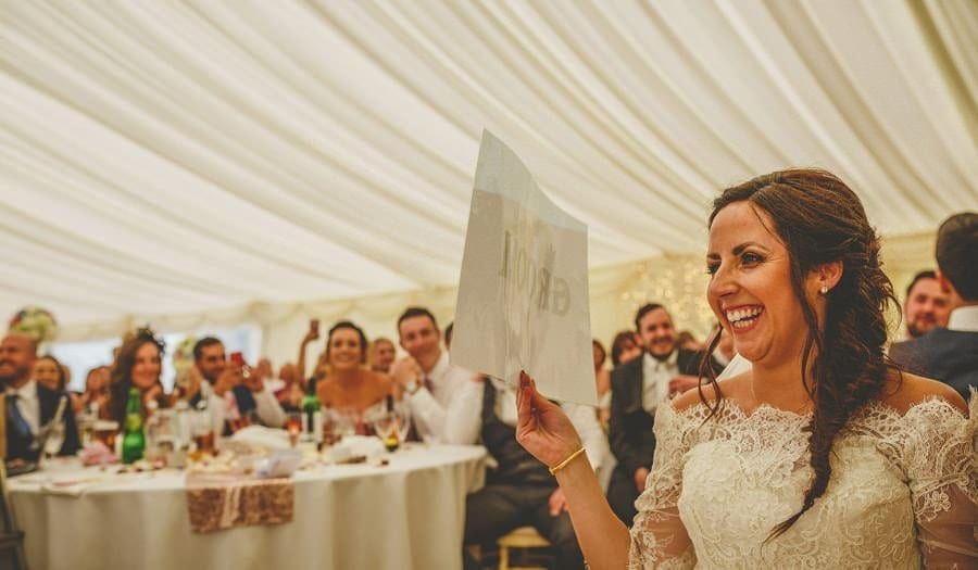 The bride lifts up a piece of paper and laughs