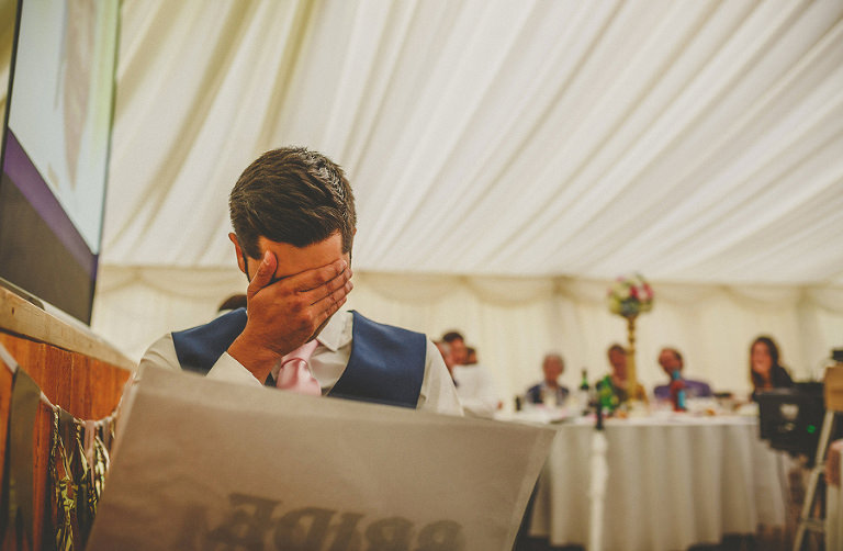 The groom holds his head in his hands