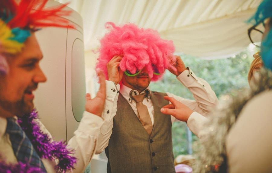 A wedding guest puts on a wig and sunglasses next to the photo booth