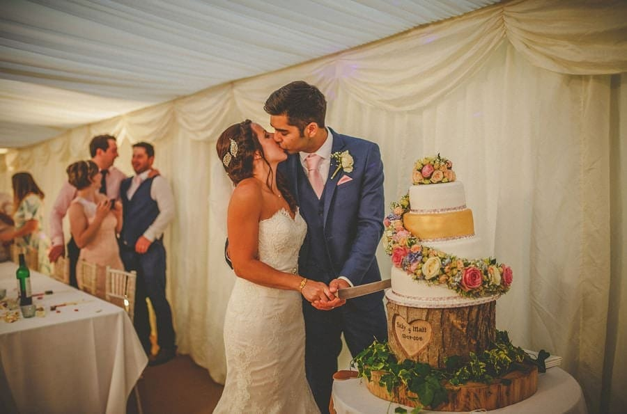 The bride and groom cut their wedding cake in the marquee at the old bridge petherton