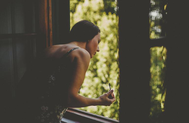 A bridesmaid looks out of the window in Villa Di Ulignano
