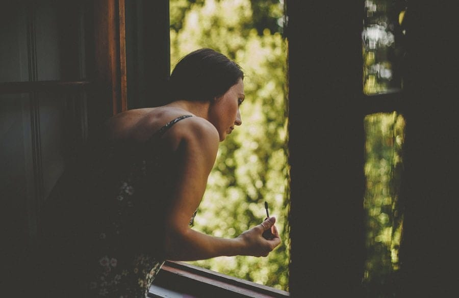 A bridesmaid looks out of the window in Villa Di Ulignano