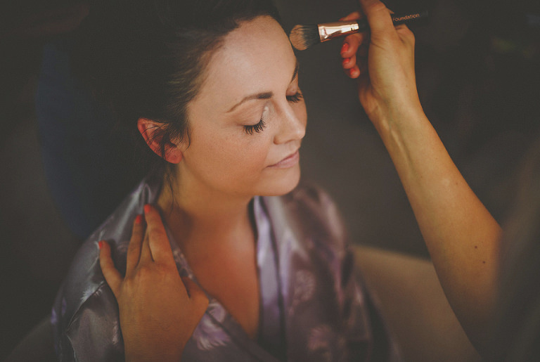 The make up artist applies foundation onto the brides face