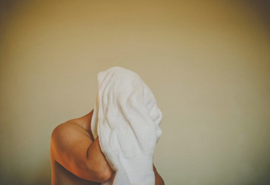 The best man puts a towel over his head coming out of the shower