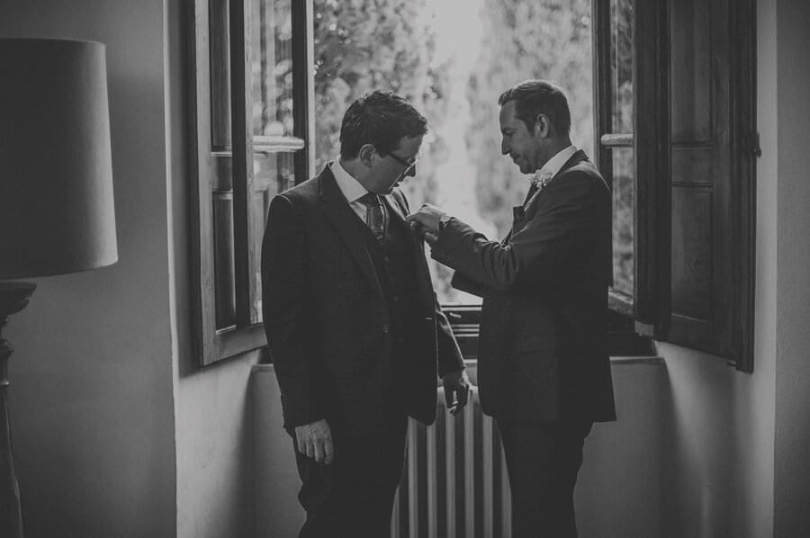 An usher helping the groom to get dressed