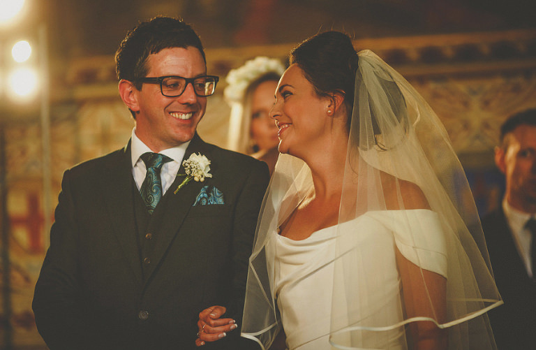 The bride smiles at the groom during the wedding ceremony at Palazzo dei Priori