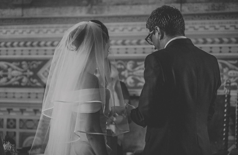 The groom places the wedding ring on the finger of the bride at Palazzo dei Priori