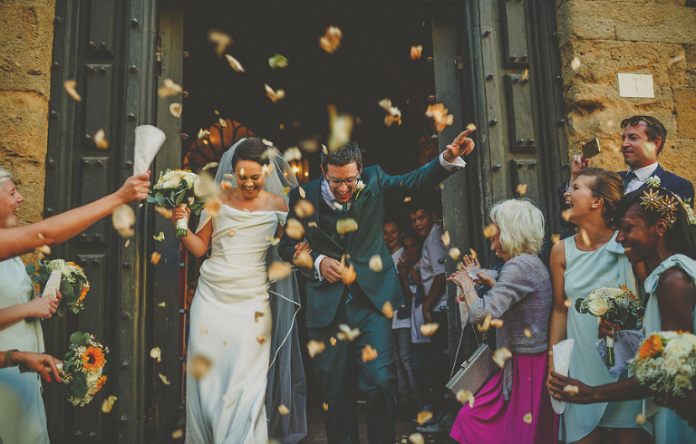 The bride and groom leave the Palazzo dei Priori as confetti is thrown into the air