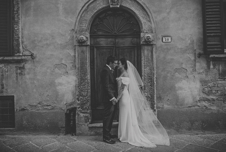 The bride and groom next to a doorway at Palazzo dei Priori