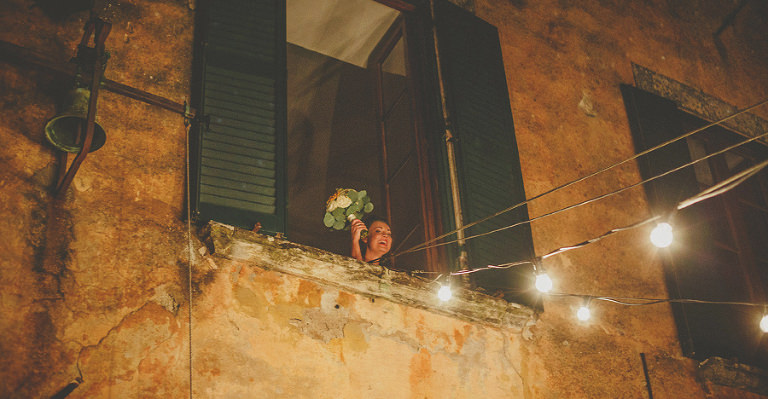 The bride appears from a window at Villa Di Ulignano to throw the bouquet