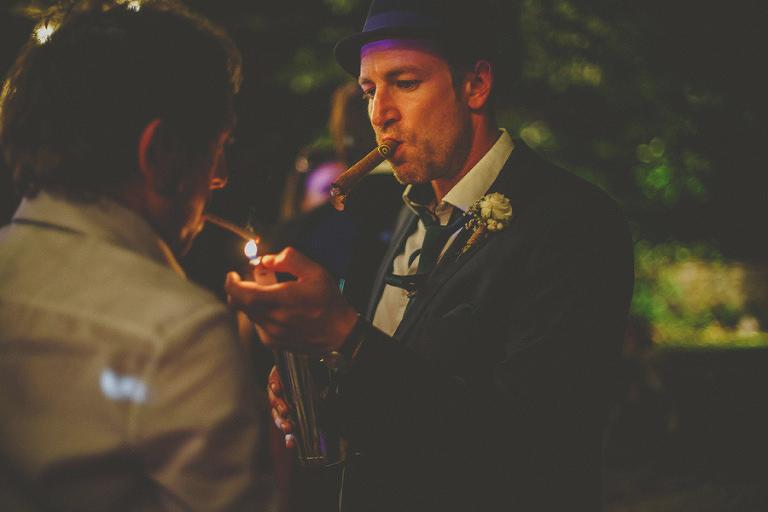 A wedding guest lights a cigar on the dancefloor for the best man