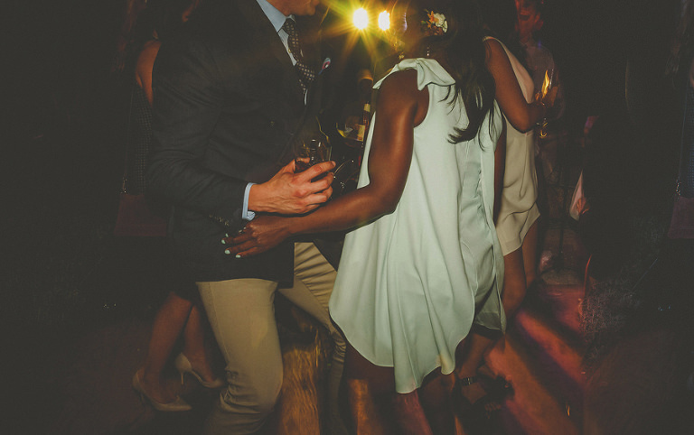 A wedding guest dances with a drink in his hand on the dancefloor at Villa Di Ulignano