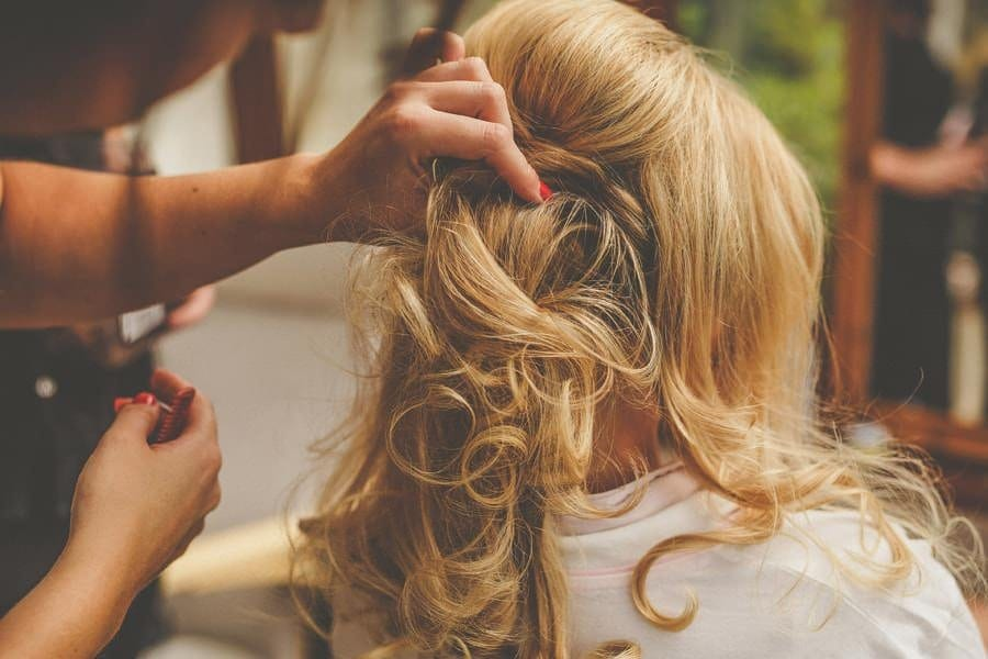 The make up artist holds the brides hair in place