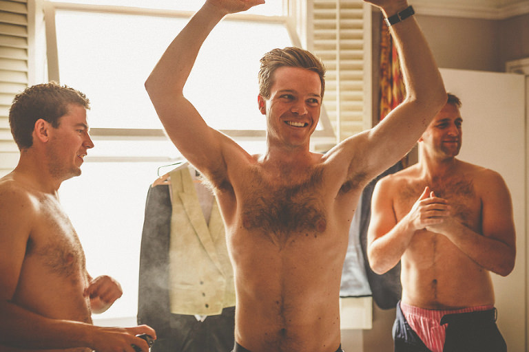 The groom raises his arms and his best man sprays deodorant on his chest