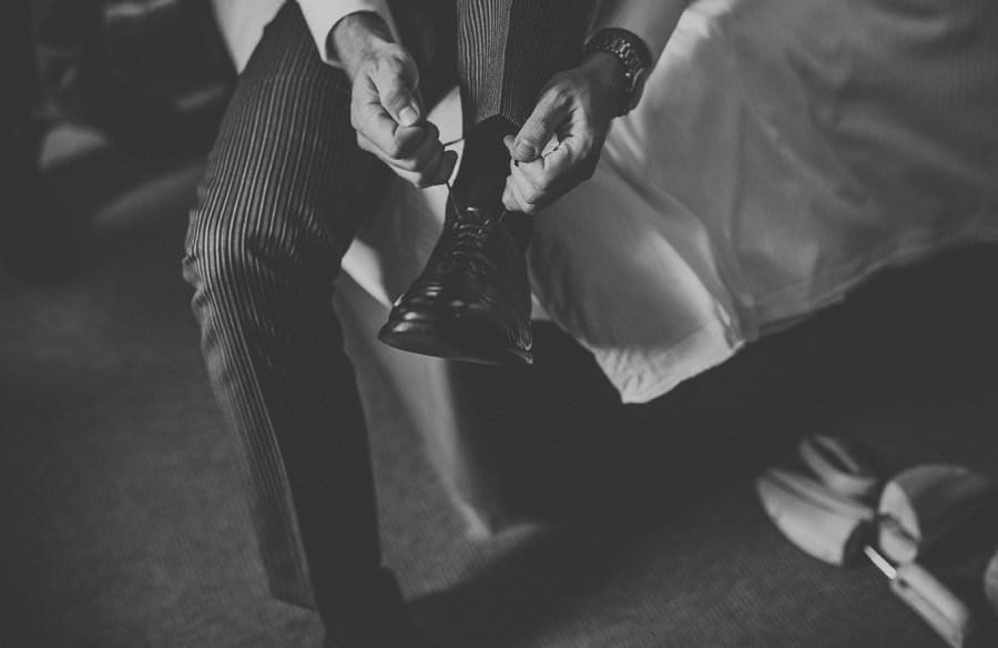 The groom puts his shoes on
