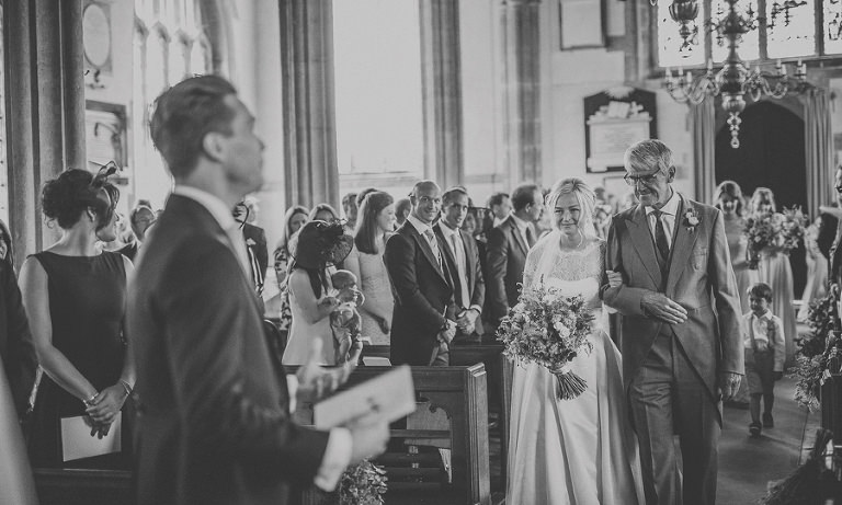 The bride and her father walk up the aisle of the church together