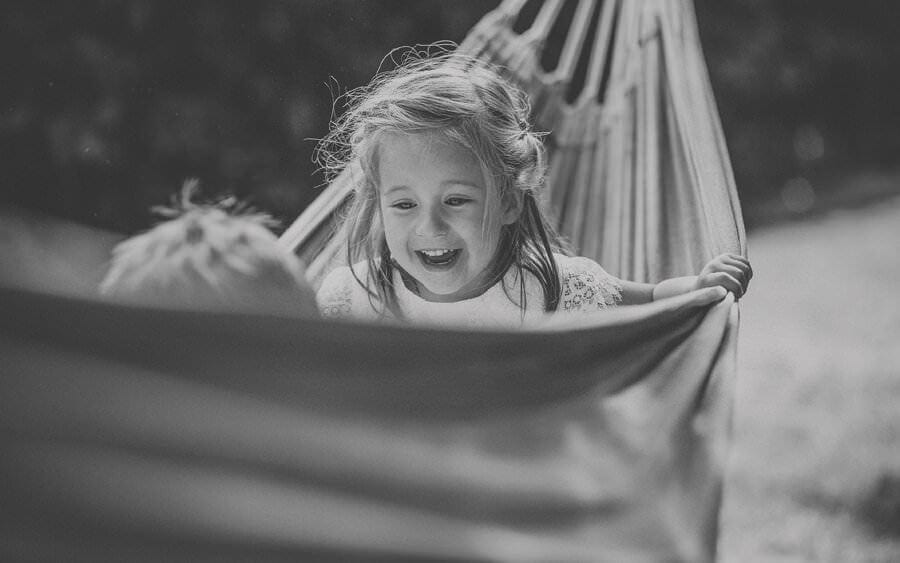 A flowergirl laughs with her brother in a hammock