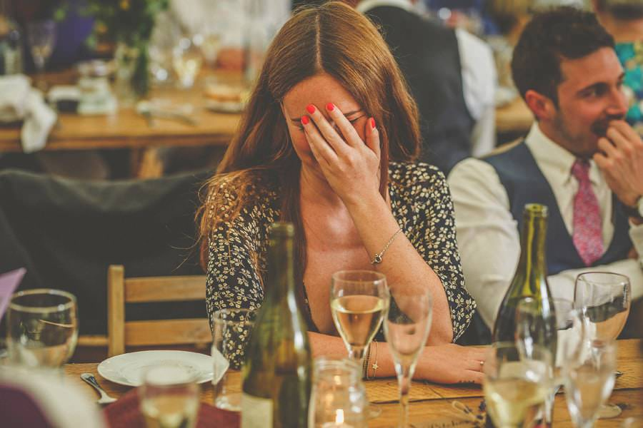 A wedding guest holds her hand to her face and laughs