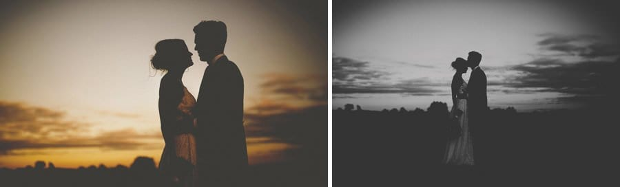 The bride and groom kiss each other as the sun goes down over the Somerset levels