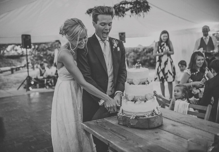 The bride and groom cut the wedding cake in the marquee