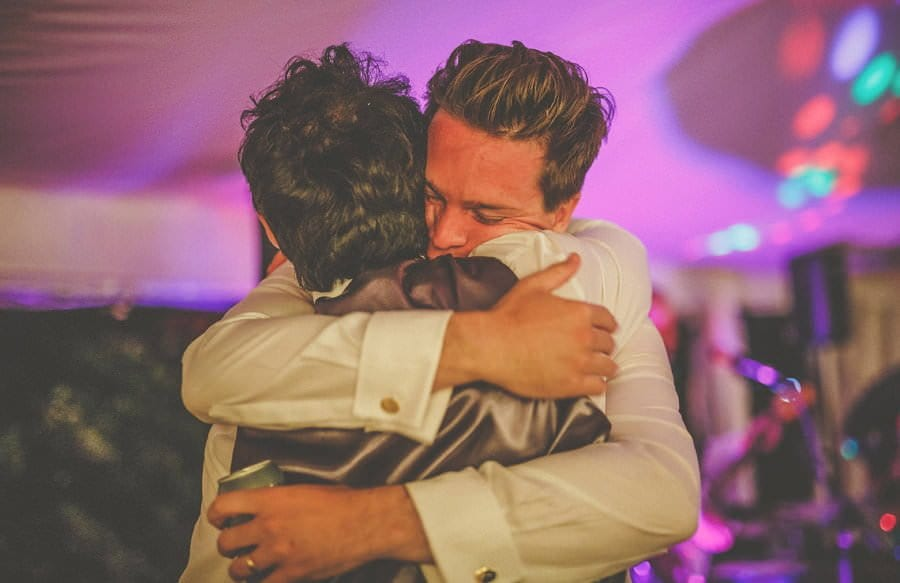 The groom and the best man embrace each other on the dancefloor in the marquee