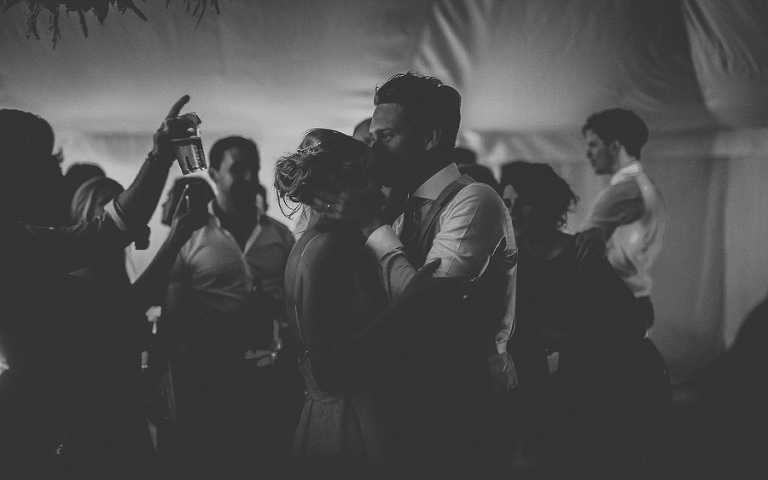 The groom kisses his bride on the dancefloor in the marquee