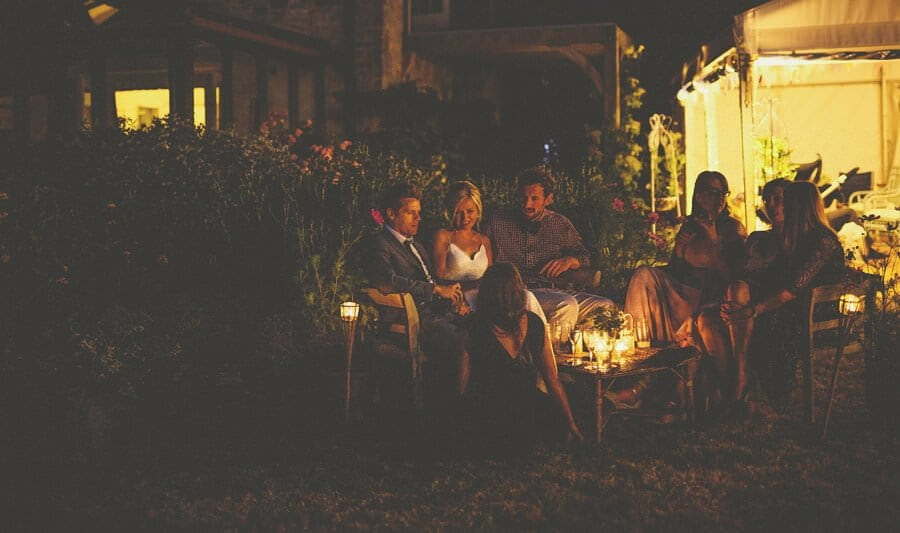 The bride sits around an open fire with her family