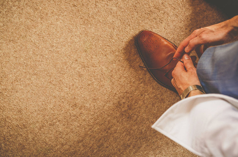 The groom puts on his shoes