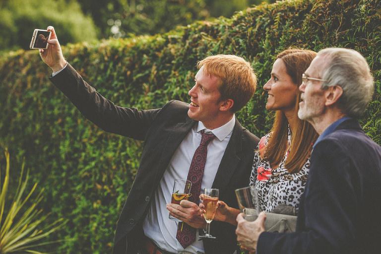 A wedding guest takes a photograph in the garden