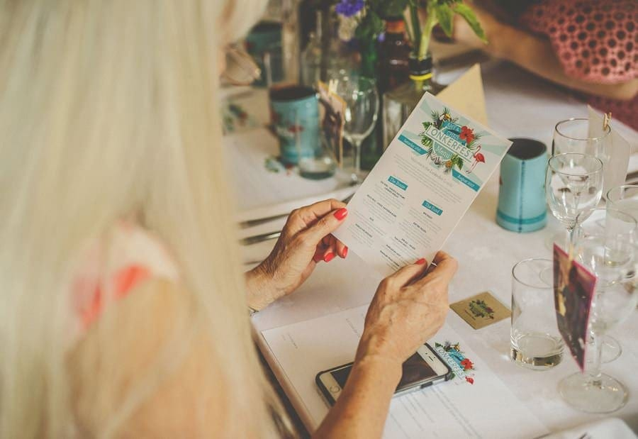 A wedding guest looks at the food menu at the dinner table