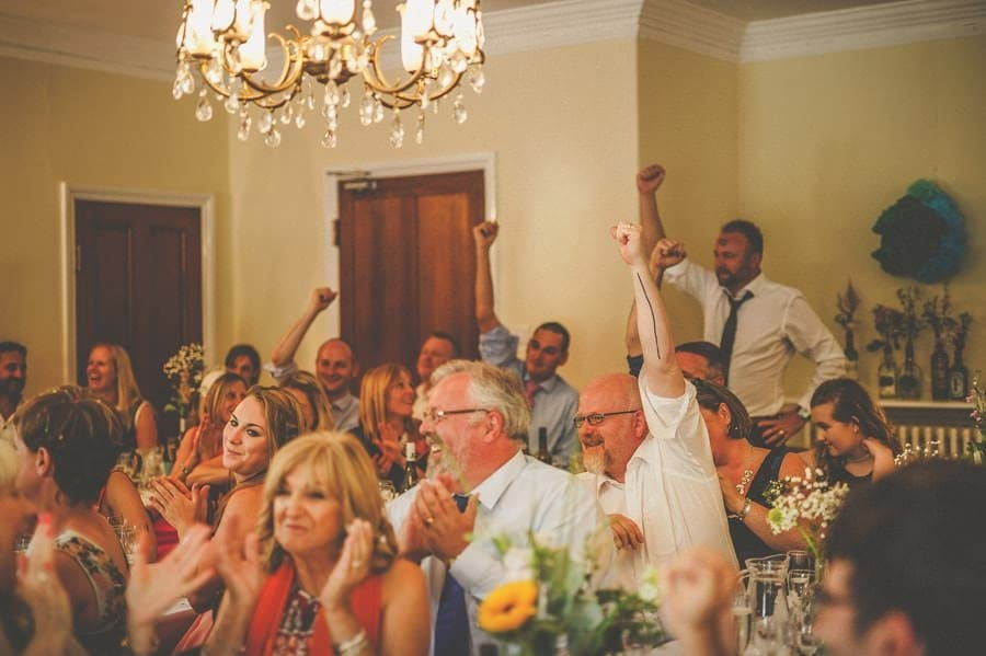 Wedding guests hold their arms up in the air