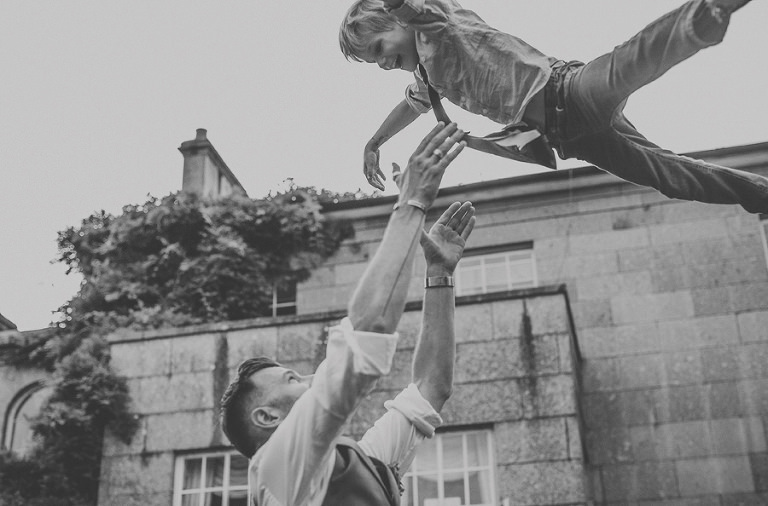 The groom lifts a family member up in the air