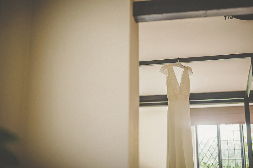 The brides dress hangs from the ceiling