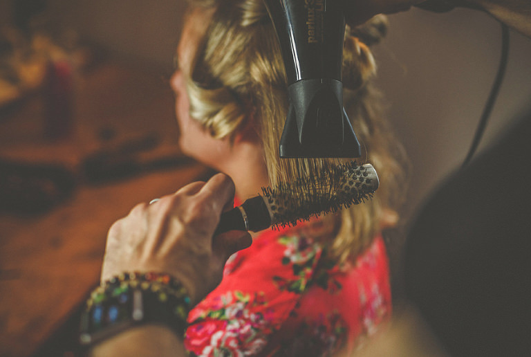 A lady curls the bridesmaids hair with a comb and hair dryer