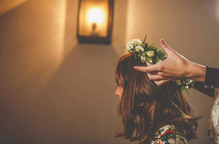 The make up artist places the floral head dress onto the brides hair