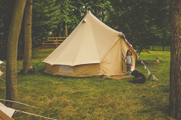 A little girl stood outside her tent with a dog lying down next to her in the camping fields
