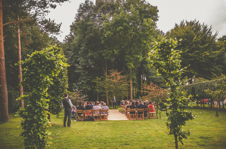 The outdoor wedding ceremony with the guests sitting on chairs
