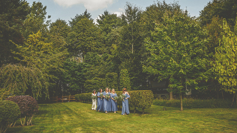 The bride and bridesmaids wait on the lawn