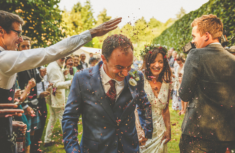 The bride and groom are showered with confetti by the wedding guests