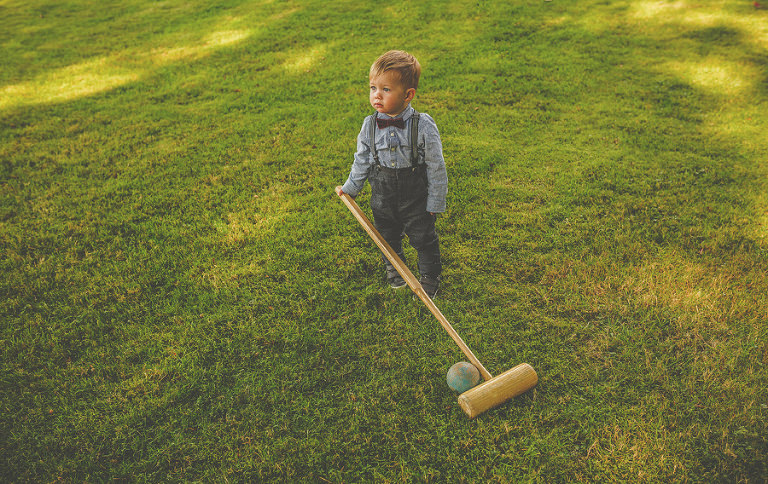 A little boy with a croquet stick stands on the lawn