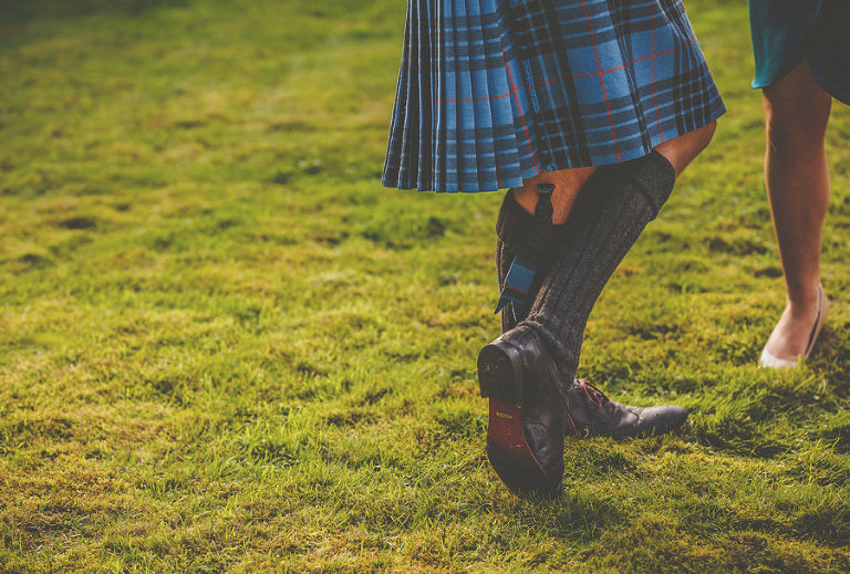 A man stands on the lawn wearing a scottish kilt