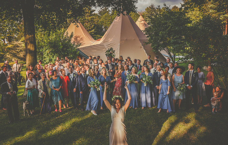 The bride throws her bouquet towards the wedding party in front of the marquee