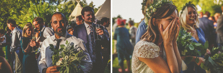 A man catches the bouquet and the bride holds her hands to her face as she laughs