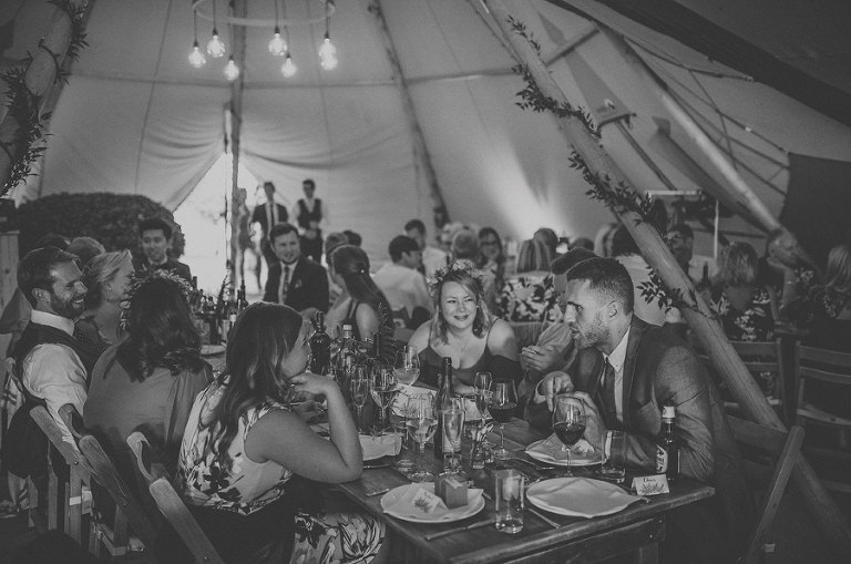Wedding guests sit down to eat in the marquee