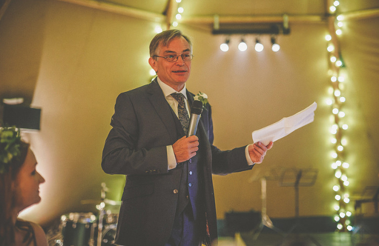 The brides father delivers his speech in front of the wedding guests in the marquee
